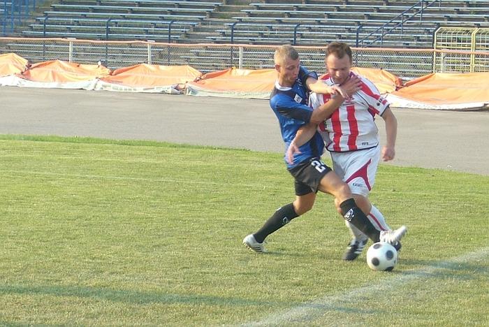 Damian Januszewski (niebiesko-czarny strój) walczy o piłkę z zawodnikiem Polonii.